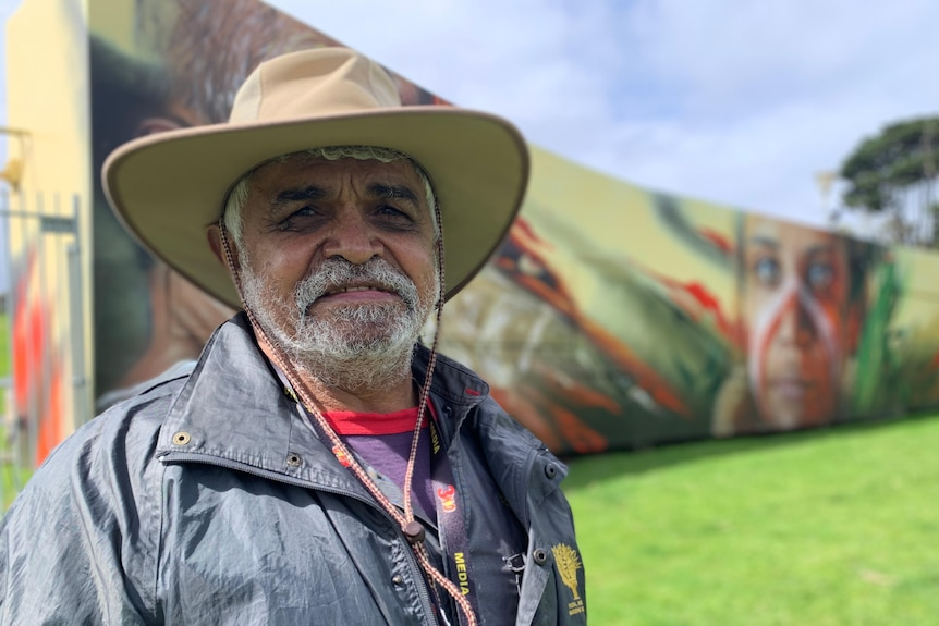 Uncle Dennis wearing a wide-brimmed hat, behind him is a long fence painted with a colourful mural.