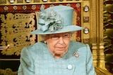 Queen Elizabeth II sitting on her throne in a green costume.