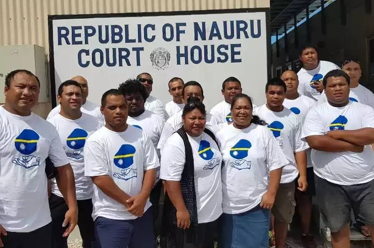 A group of Nauruan men and women wear matching white t-shirts in front of the court room.