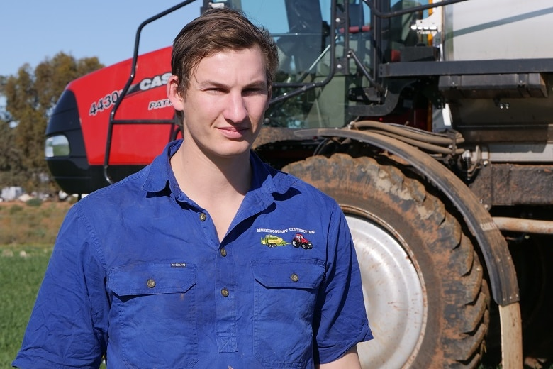 A young man stand in front of large crop spraying machinery, in a field of newly germinating crop.