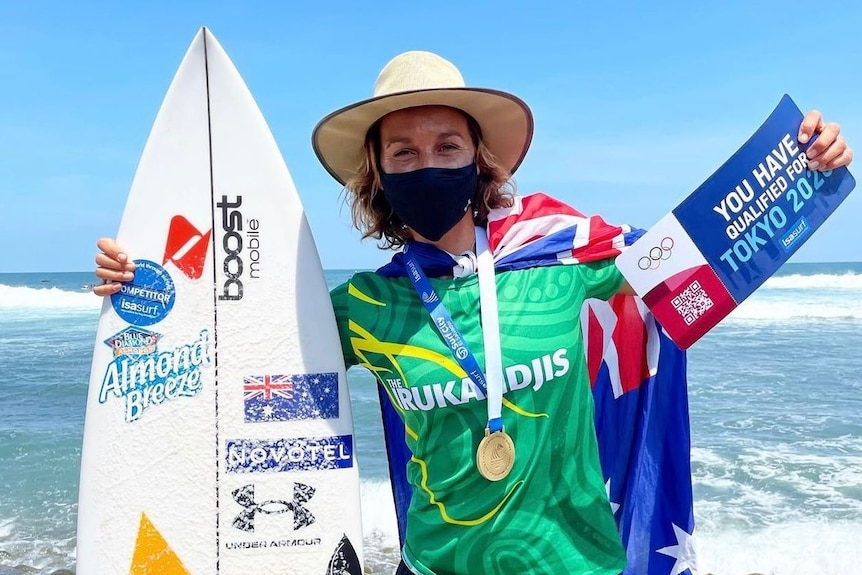 Woman standing wearing face mask holding a surf board and a large ticket saying she has qualified for the OIympics