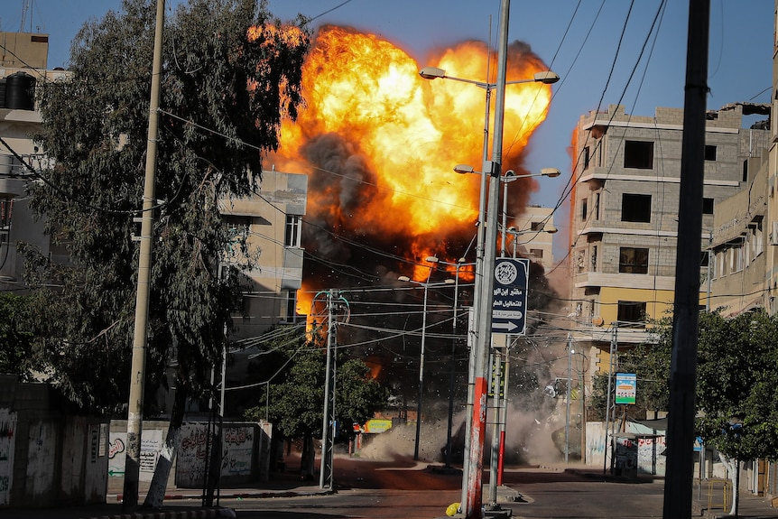 An explosion is seen among buildings and powerlines.