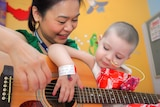 Paediatric music therapist Maggie Leung with a young patient at Lady Cilento Children's Hospital, Brisbane.