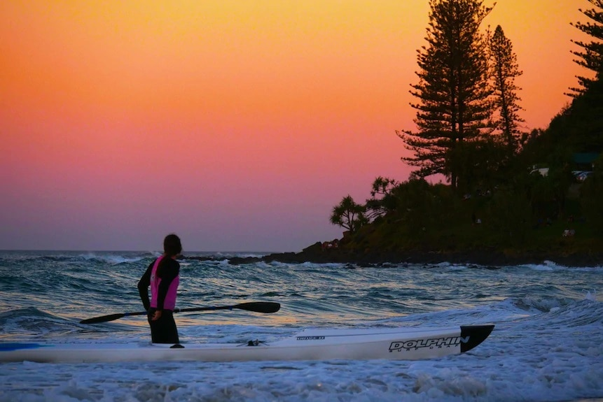 A man is silhouetted against the sunset at Burleigh Beach
