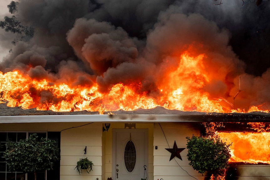 Roof on fire of a home in Paradise where thousands of structures were lost.