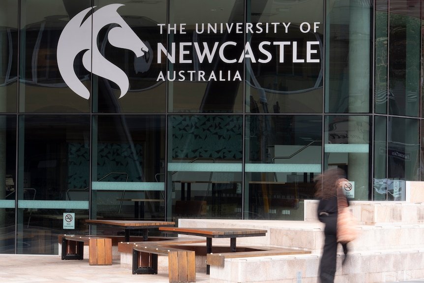 Exterior of a University of Newcastle building with an out-of-focus person walking past