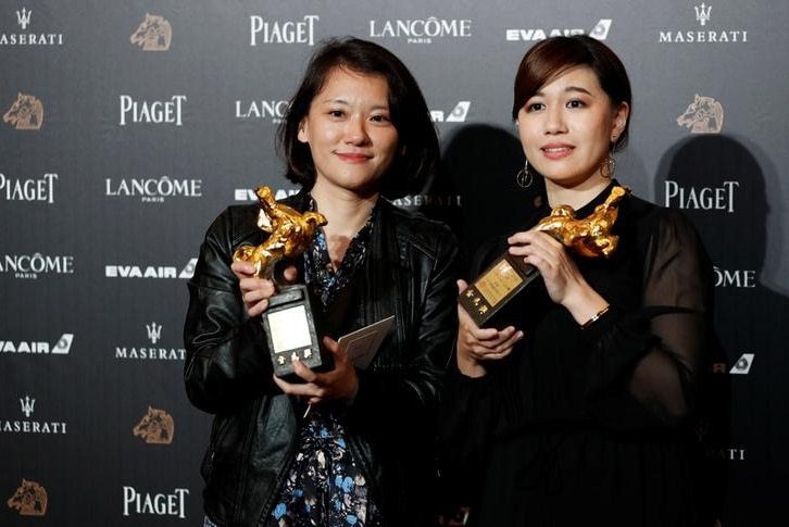 Two women hold trophies.