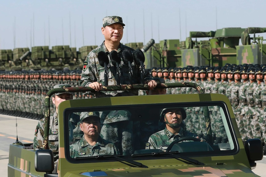 Chinese President Xi JinPing stands on a military jeep in full camouflage gear