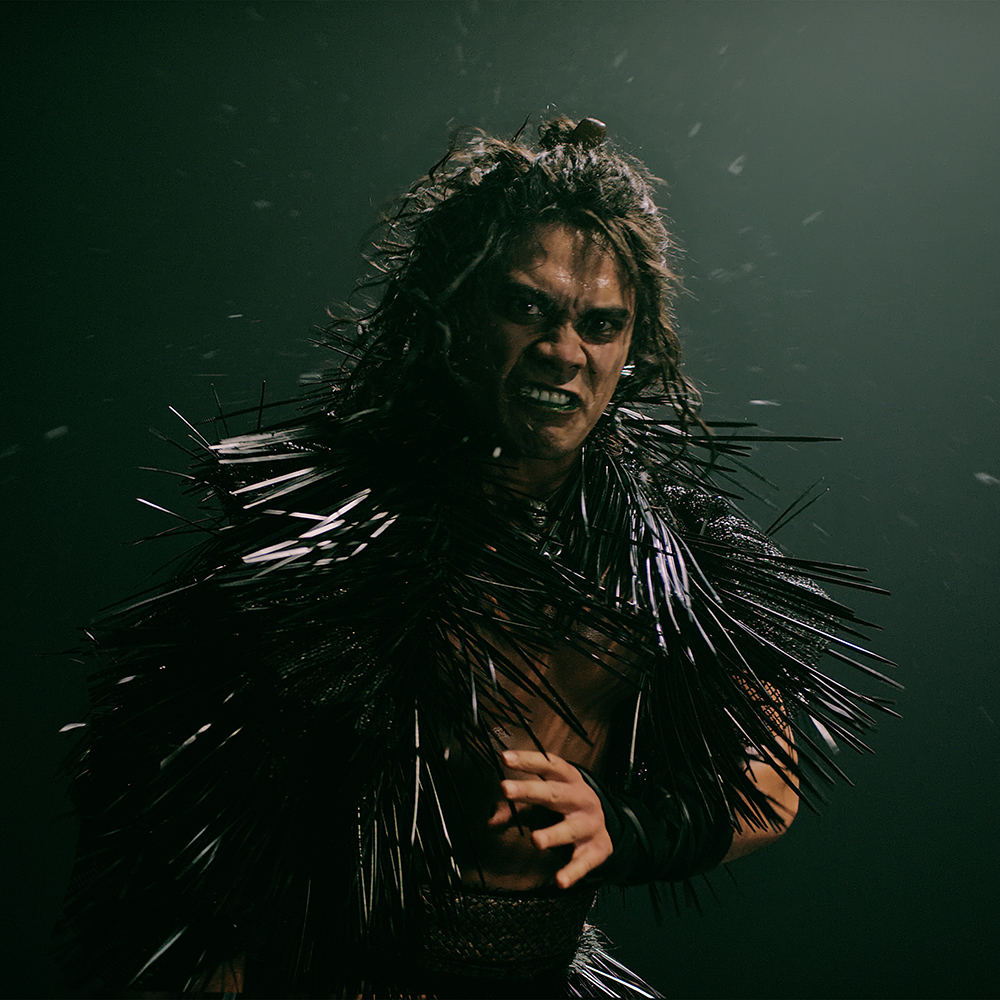 A man with long dark hair with fierce expression wears black spikey garment and stands ready for a physical confrontation.