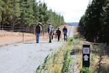 A group makes their way down the memorial walking track.