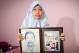 A little girl in a veil holds framed photographs of her late mother and father