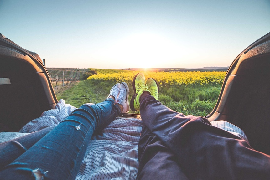 Couple relax in the back of their car looking at the view to depict a story about women experiencing baby panic.