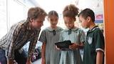 Craig Reucassel with Oatlands Primary School students holding ipad