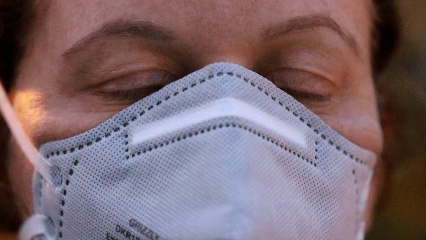 Unidentified female wearing a respiratory mask, with eyes closed.