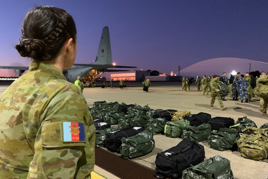 A woman wearing a camouflaged ADF uniform looks over a row of duffel bags and people getting off a plane.