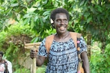 Susan Paai smiles as she holds a stick with a basket full of vegetables on her back.