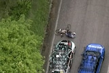 A man lies on the ground in front of a car with his bike next to him as seen from above.