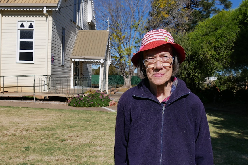 An elderly lady wearing a purple jacket and a red and white striped hat standing outside a church.