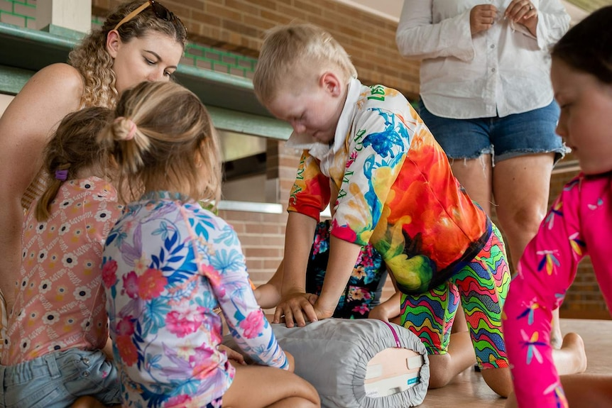 A young boy performs CPR on a dummy as other children look on.