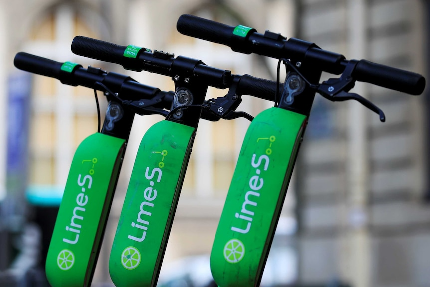 Lime scooters lined up along the footpath.