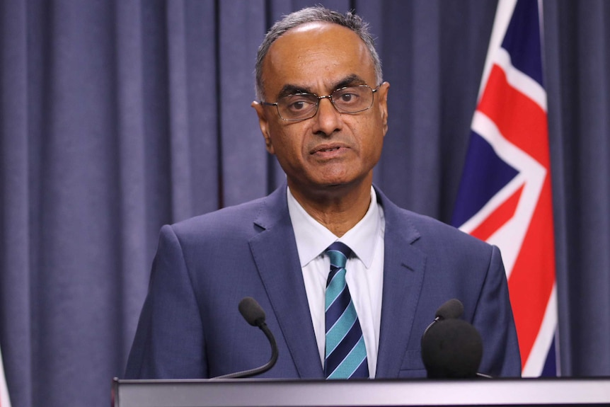 A mid shot of WA chief health officer Tarun Weeramanthri speaking at a media conference in front of an Australian flag.