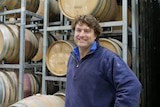 A man standing in front of wine barrels.