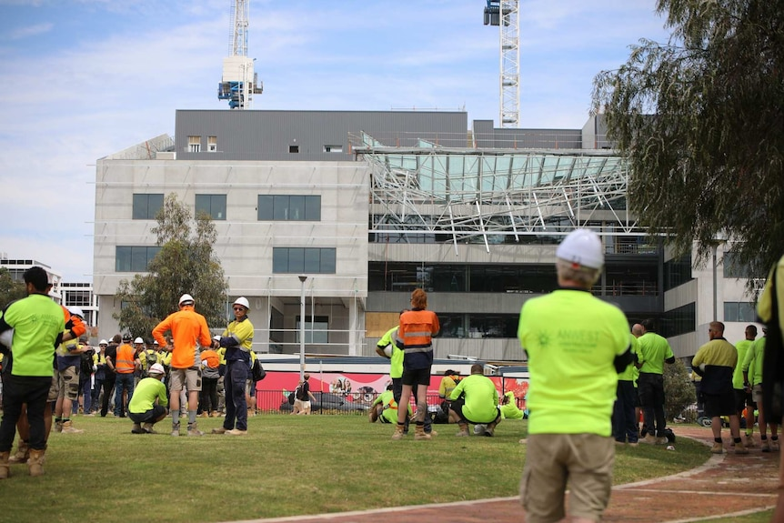 Workers in hi-vis clothing gathered on grass at Curtin University looking at the collapsed roof of a building.