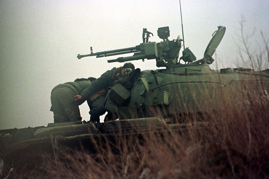 Men crouch in front of a tank