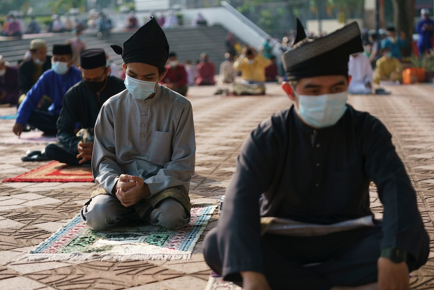 Men wearing traditional Malay attire and face masks sit in a socially-distanced manner at a mosque