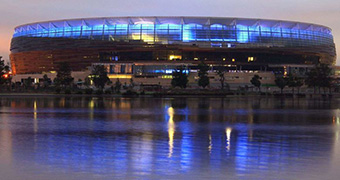 Perth Stadium illuminated at twilight and reflected in the Swan River.