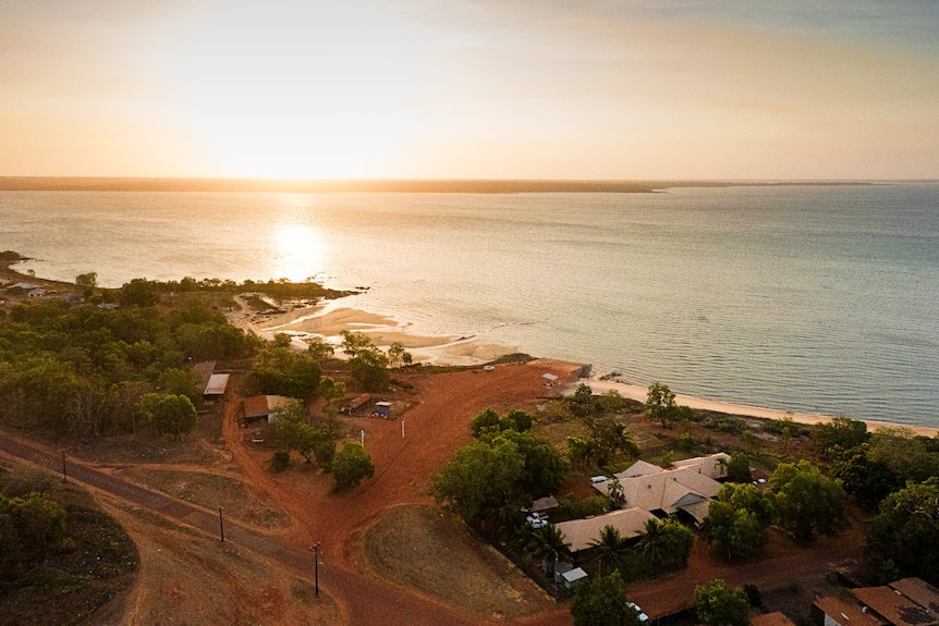 An aerial view of a setting sun on a small settlement next to a tropical bay