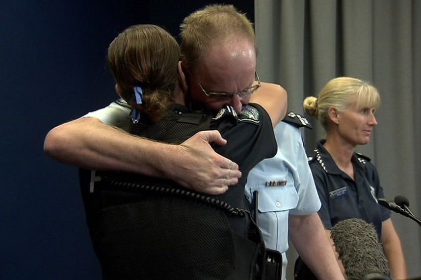 Superintendent David Johnson comforts Senior Sergeant Lukia Serafim at a press conference about a Christmas Day double fatality.