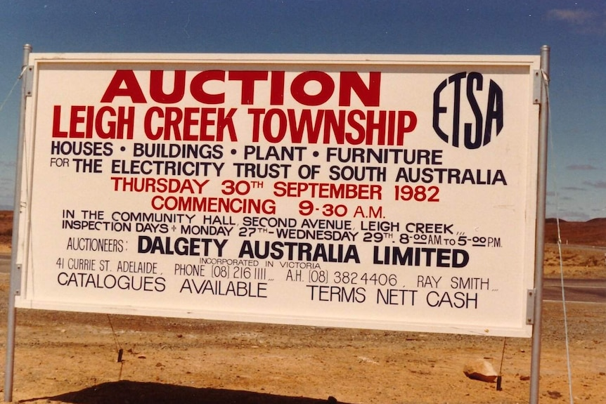 A large white sign with red letters saying 'auction Leigh Creek township'.