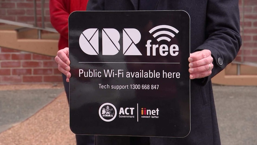 A man holds a sign that reads 'CBRfree Public Wi-Fi available here'.