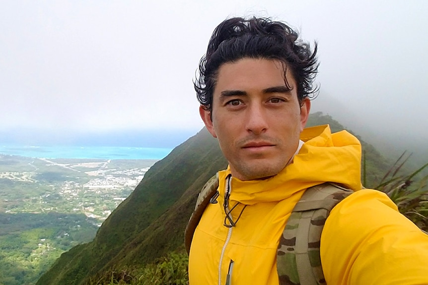Nathan Crumpton takes a selfie high up in the hills with a view to mountains and water behind him.