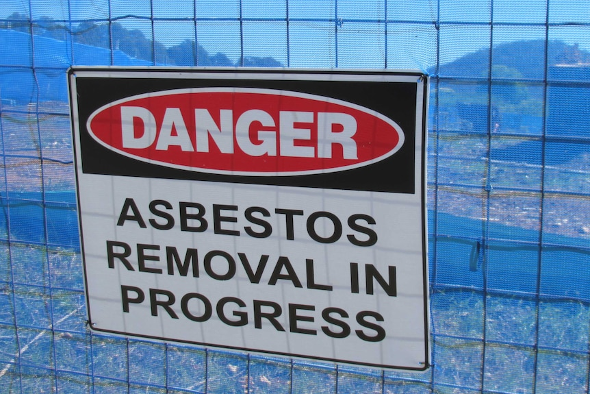 A sign on a fence saying 'Danger, asbestos removal in progress'