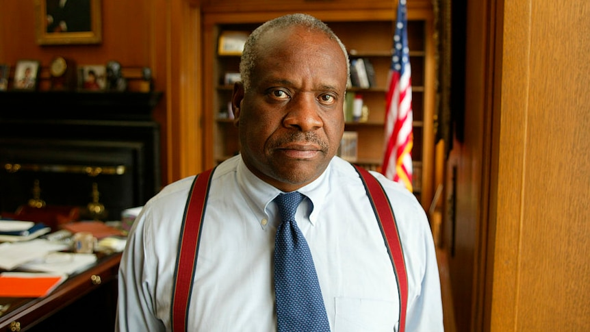 A younger Clarence Thomas poses for a photograph in his office