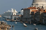 A cruise ship in the background is nearly as large as a large dome in Venice, while gondolas and vaporetto pass through a canal.