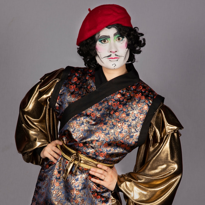 Kay wears a red beret and a handmade outfit with billowing gold sleeves.