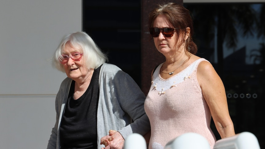 Two ladies holding hands and leaving the court house in Darwin.