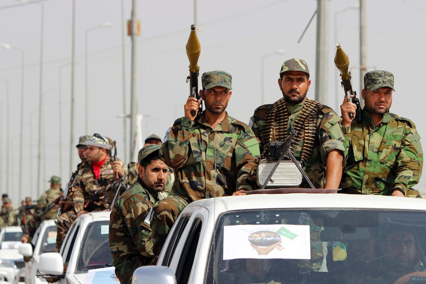 Fighters loyal to Shiite cleric Moqtada al-Sadr sit in the back of vehicles with rocket launchers during a parade in Basrah