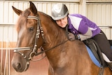 Danyele Foster leans forward in the saddle to embrace the horse she trains with, Bengala.