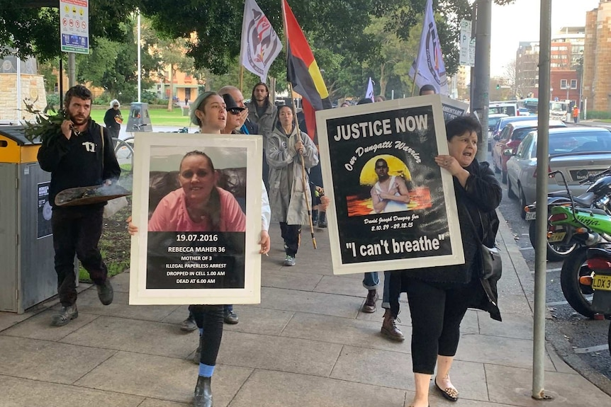people marching in support of Rebecca Maher, carrying signs and Aboriginal flag