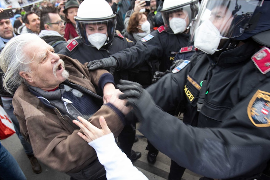 A protester debates with the police during a demonstration against COVID-19 restrictions in Vienna, Austria.