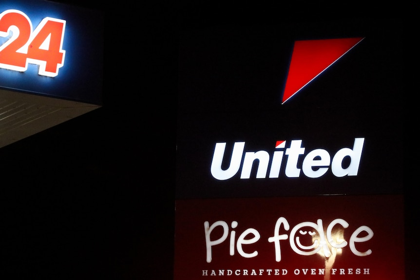 United Petrol Station and Pie Face sign at night.
