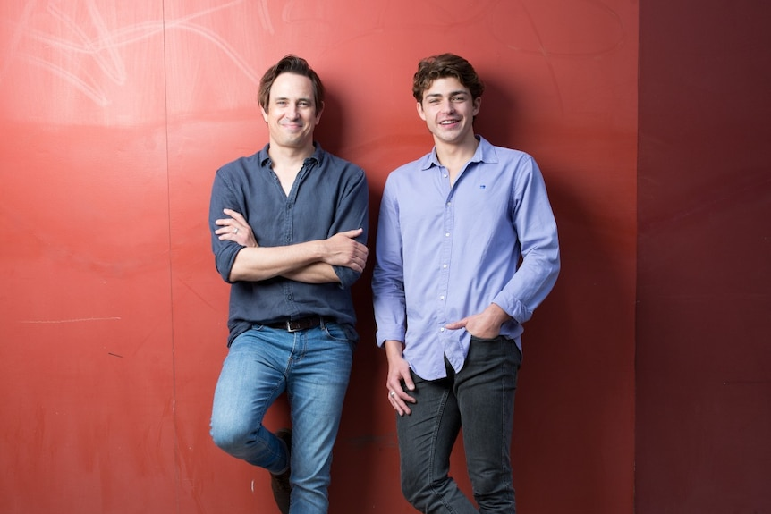 A 40-something man and a 20-something man stand next to each other, smiling proudly and leaning against a red wall