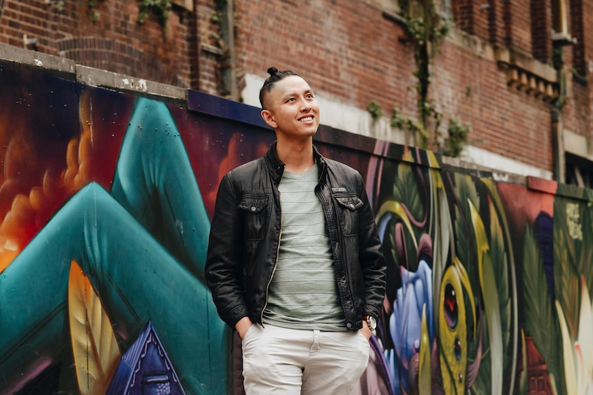 Mid-20s Vietnamese Australian man Peter Nguyen standing in front of graffiti and brick wall, looking up and smiling slightly.