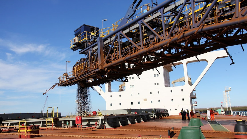 A horizontal crane pumps ore into the hold of a loading ship with superstructure visible in the Pilbara in 2012.
