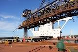 Horizontal crane pumping ore into ship in Pilbara