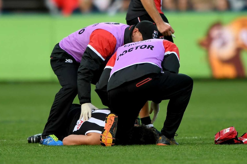 St Kilda's Dylan Roberton lies on the ground after collapsing against Geelong